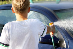 Young boy washing the car with hose Royalty Free Stock Photos