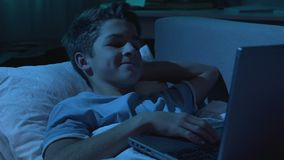 Young boy watching adult film at night on laptop, looking around, parent control stock video footage