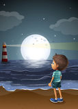 A young boy watching a fullmoon at the beach Stock Photos