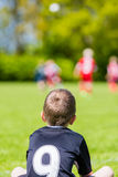 Young boy watching a kids soccer match. Young boy watching his team mates play a kids soccer match on soccer field with green grass Royalty Free Stock Photography
