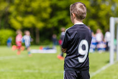 Young boy watching a kids soccer match. Young boy watching his team mates play a kids soccer match on soccer field with green grass Stock Images