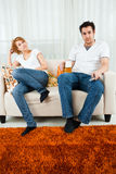 Young boy watching television with a young girl Stock Photos