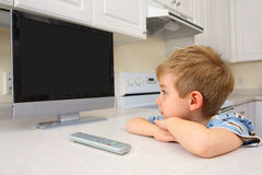 Young boy watching tv in a kitchen Royalty Free Stock Photos