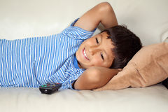 Young boy watching TV. With remote control Royalty Free Stock Photos