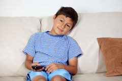 Young boy watching TV. With remote control Royalty Free Stock Images