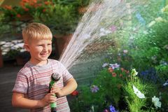Young boy watering flowers. Young cute boy kid child four years old, having fun with water, watering flowers, leisure activity outdoor Royalty Free Stock Image