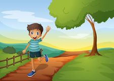 A young boy waving his hand while running Stock Image