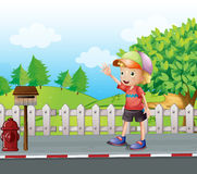 A young boy waving near the mailbox at the road Royalty Free Stock Image