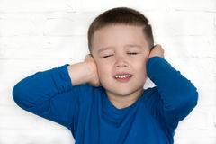 Young boy wearing blue jacket with his eyes closed covering his ears to hear Stock Images