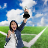 Young boy wearing blue jacket hood. And holding soccer trophy Royalty Free Stock Images