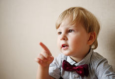 Young Boy Wearing Bow Tie and Pointing to the Side Stock Photo