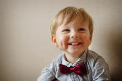 Young Boy Wearing Bow Tie Smiling and Looking Up. Against Plain Wall with Copyspace Royalty Free Stock Photos