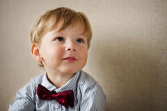 Young Boy Wearing Bow Tie Smiling and Looking Up. Against Plain Wall with Copyspace Stock Photo