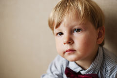 Young Boy Wearing Bow Tie Smiling and Looking Up. Against Plain Wall with Copyspace Royalty Free Stock Image