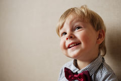 Young Boy Wearing Bow Tie Smiling and Looking Up. Against Plain Wall with Copyspace Royalty Free Stock Photo
