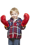 Young boy wearing boxing gloves smiling. On white background Royalty Free Stock Image