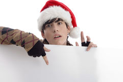 Young boy wearing christmas hat indicating placard. With white background Royalty Free Stock Photo