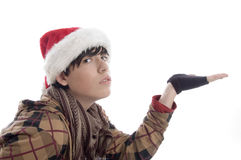 Young boy wearing christmas hat showing palm. On an isolated background Stock Photo