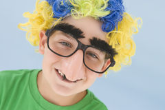 Young boy wearing clown wig and fake nose smiling. At camera Royalty Free Stock Photo