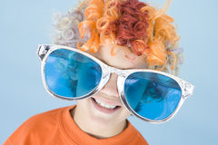 Young boy wearing clown wig and sunglasses smiling. At camera Stock Image