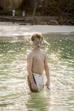 Young boy wearing a diving mask is walking at the beautiful beac Stock Images