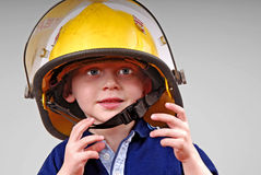 Young Boy Wearing Fireman's Helmet Stock Photos