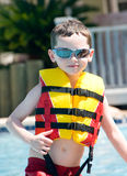 Young boy wearing flotation device. Young boy in pool wearing safety flotation royalty free stock images