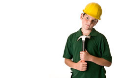 Young boy - future construction worker. A young boy wearing a hard hat and holding a hammer, isolated on a white background Royalty Free Stock Photos
