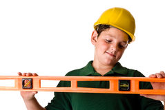 Young boy - future construction worker. A young boy wearing a hard hat and holding up a level, looking at the bubble. Sweat beads can be seen on his face from Royalty Free Stock Photography
