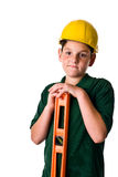 Young boy - future construction worker. A young boy wearing a hard hat and leaning on a level. Sweat beads can be seen on his face from the hard construction Stock Photo