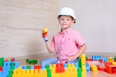 Young boy wearing hardhat playing indoors Royalty Free Stock Photos