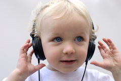 Young boy wearing headphones. Young boy with headphones against white background Stock Image
