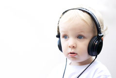 Young boy wearing headphones III. Young boy with headphones against white background. Big blue eyes Stock Photo