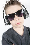 Young boy wearing headphones listening music in stock photos