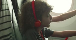 Young boy trying to adjust his seat back entertainment touchscreen on a plane stock video