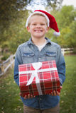 Young Boy Wearing Holiday Clothing Holding Christmas Gift Outside Royalty Free Stock Photo