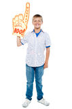 Young boy wearing a large foam hand. Full length portrait of a stylish young boy wearing a large foam hand. Boo and hurray Royalty Free Stock Photos