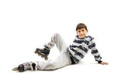 Young boy wearing roller skates sitting on floor, posing Royalty Free Stock Photos