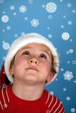 A young boy wearing a santa hat. Looking at snowflakes Royalty Free Stock Images