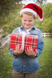Young Boy Wearing Santa Hat Holding Christmas Gift Outside Royalty Free Stock Images