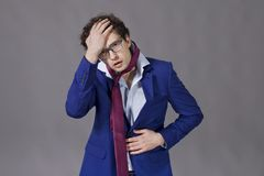Guy wearing in suit and necktie feeling ill. Young boy wearing in suit, necktie and with glasses feeling bad royalty free stock photo