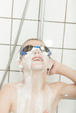 Young boy wearing swimming goggles in a shower Stock Photos