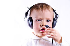 Young boy wearing telephone headset. The serious little boy in ear-phones with a microphone in call center answers a call on a white background Royalty Free Stock Image