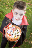 Young boy wearing vampire costume on Halloween. Young boy outside wearing vampire costume on Halloween holding a pumkin of sweets Royalty Free Stock Image
