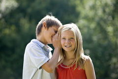 A young boy whispering to a young girl Royalty Free Stock Image