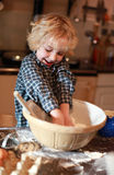 Young boy who is mixing flour Royalty Free Stock Images