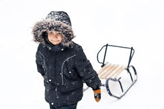 Young boy in winter suit pulling sledges Royalty Free Stock Images