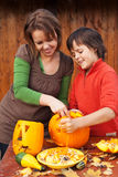 Young boy and woman carving a jack-o-lantern Stock Images