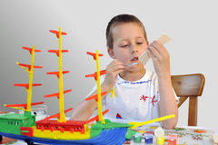 Young boy - woodcraft ship painting, focused Stock Photography