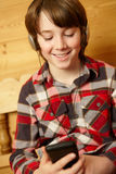 Young Boy On Wooden Seat Listening To MP3 Player Royalty Free Stock Image